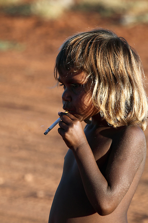 girl at a bush footy match, grabbed her mums smoke and pretended to have a puff.