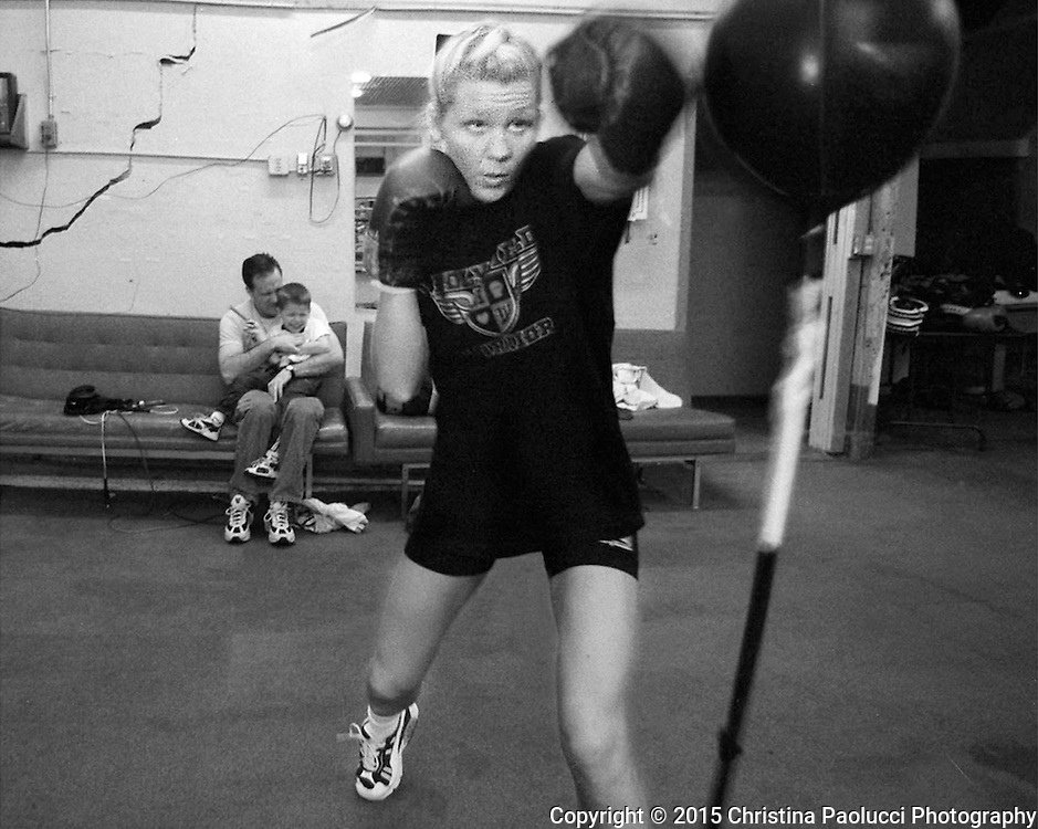 Lorie Mueller concentrates on a double-end bag at the Fourth Street Boxing Gym while her husband, Rick entertains their 4-year-old son Christian.