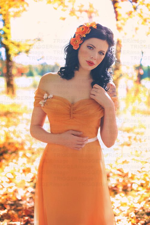 Young woman with red hair<br /> A beautiful young brunette woman stands in a lovely autumn scene, wearing a fancy regency dress with a soft expression on her face