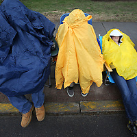 (Wellesley, MA - 4/20/15) Cousins Matthew Sahagian, 15, Cody Delvecchio, 15, and Travis Delvecchio, 12, huddle under ponchos while waiting for the Boston Marathon to begin, Monday, April 20, 2015. Staff photo by Angela Rowlings.