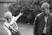 Neville playing with braces with Lee in a garden, Hawthorne Road, High Wycombe, UK, 1980s.