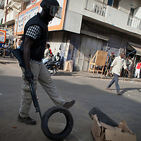 Policeman cleans street barricades constructed by Anti-government protesters in central Dakar, Senegal Friday, Feb. 17, 2012. Police used tear gas and rubber bullets to disperse protesters who had planned to go ahead with a sleep-in Thursday at Place de l'Obelisque, even though the government had banned the demonstration being held one week before the country's presidential election.