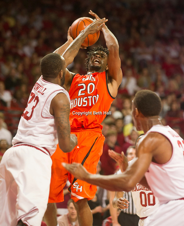 Nov 9, 2012; Fayetteville, AR, USA; Sam Houston Bearkats forward James Thomas (20) takes a shot over Arkansas Razorbacks guard DeQuavious Wagner (23) during the first half of a game at Bud Walton Arena. Mandatory Credit: Beth Hall-US PRESSWIRE