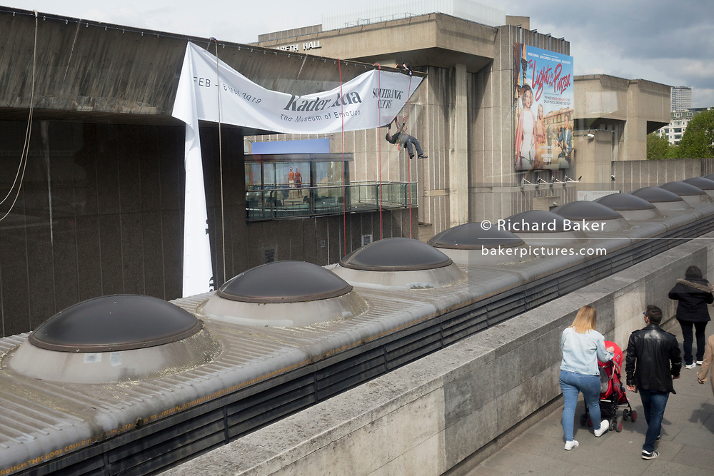 """A contractor hangs from the roof to position a banner for a new exhibition of the artist Kader Attia, of the Hayward Gallery on the Southbank, on 7th May 2019, in London, England. Kadar Attia works, """"In sculptures, installations, collages, videos and photographs that move 'back and forth between politics and poetry', Attia inventively explores the ways in which colonialism continues to shape how Western societies."""""""