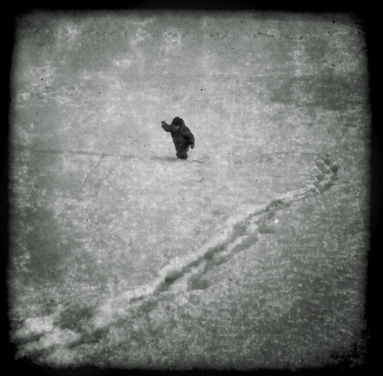 A small boy walking through the snow