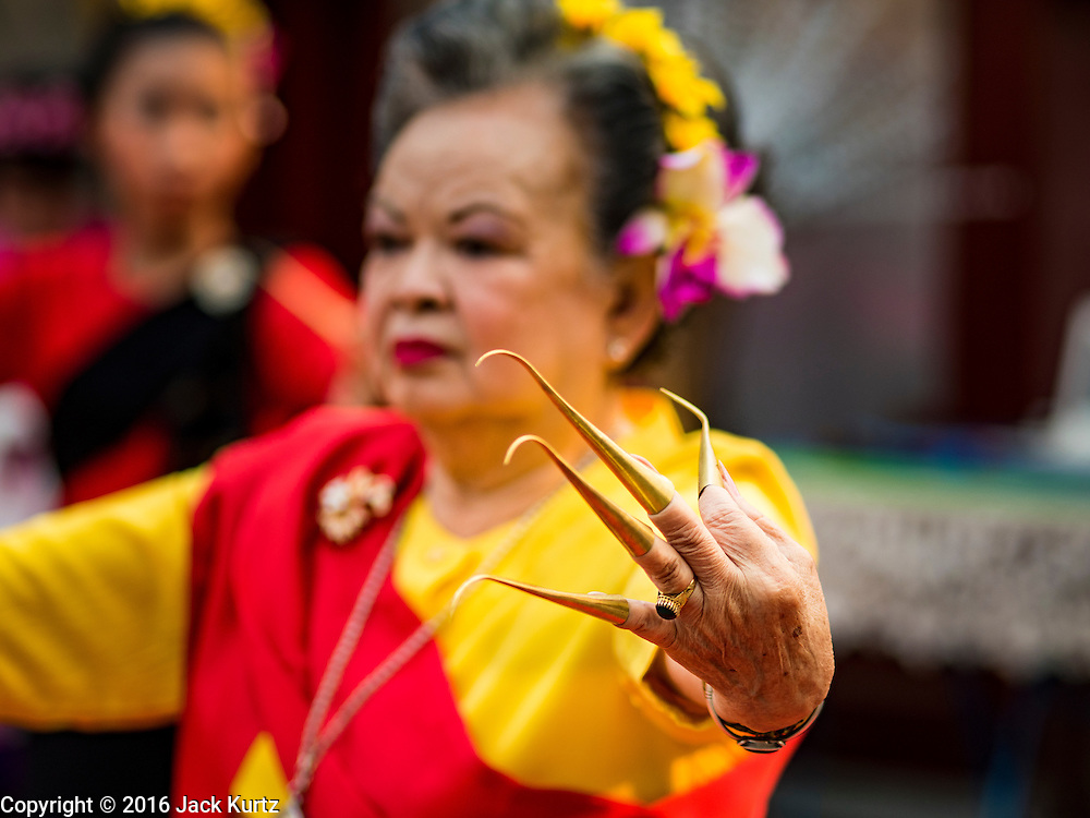 """03 APRIL 2016 - CHIANG MAI, THAILAND: A Thai woman performs a traditional northern Thai dance at the dedication of the ubosot, or ordination hall, at Wat Sri Suphan. Wat Sri Suphan is also known as the """"Silver Temple"""" because of its silver ubosot, or ordination hall. The temple is more than 500 years old but the silver ordination hall was recently remodeled. The ordination hall is covered in silver and the interior is completely done in silver and gold. It's traditionally served as the main temple for the silversmiths of Chiang Mai, whose community is around the temple.     PHOTO BY JACK KURTZ"""