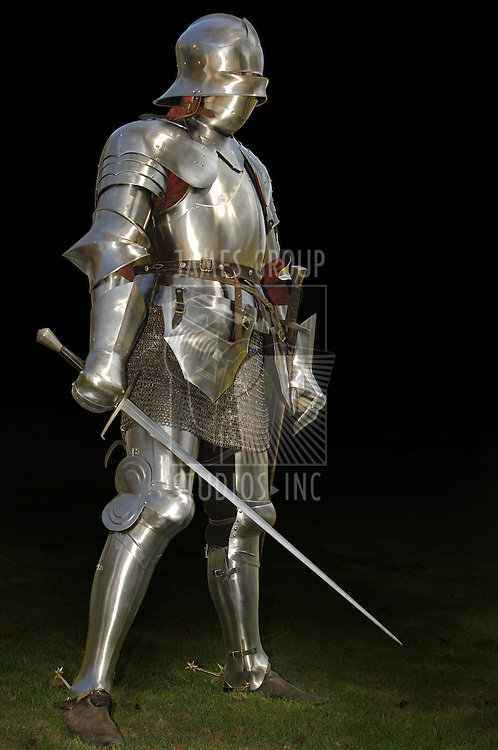 Mediaeval knight in shining armour of the 15th century standing outside with sword. Isolated on a dark background with clipping path