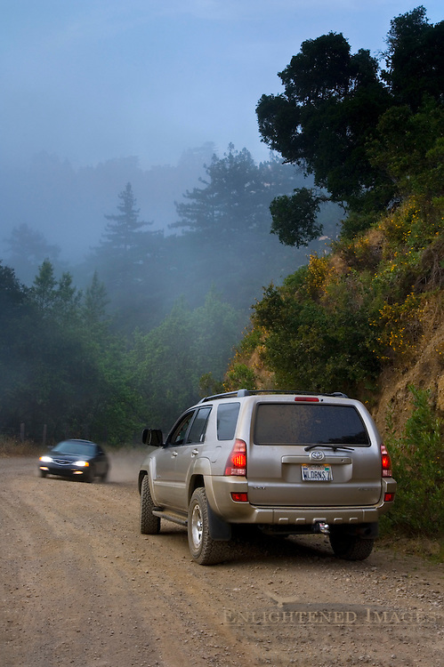 Car coming around a corner past Toyota 4-Runner SUV 4WD and coastal fog along the old coast dirt road, Big Sur Coast, Monterey County, California