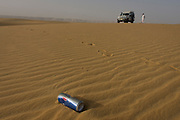 Human presence in the form of a drinks can and footprints left in the sand of dunes at al-Galamun, near Dahkla Oasis, Western Desert, Egypt. The Western Desert covers an area of some 700,000 km2, thereby accounting for around two-thirds of Egypt's total land area. Dakhla Oasis is one of the seven oases of Egypt's Western Desert (part of the Libyan Desert). It lies in the New Valley Governorate, 350 km (220 mi.) and measures approximately 80 km (50 mi) from east to west and 25 km (16 mi) from north to south.