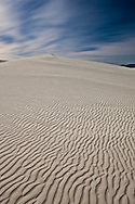 A large dune in White Sands National Monument lit by a full moon on a calm spring evening