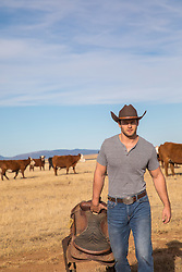 handsome cowboy with a saddle on a cattle ranch
