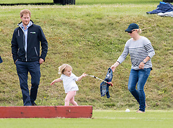 TETBURY - UK - 18th June 2016: Prince William, HRH The Duke of Cambridge plays a charity polo match at the Beaufort Festival of Polo near Tetbury in Gloucestershire.<br /> <br /> Prince William was watched by his brother Prince Harry and Zara Phillips with her daughter Mia.<br /> <br /> Prince Harry takes cover and avoids the polo mallet being swung around by Mia.<br /> Photograph by Ian Jones