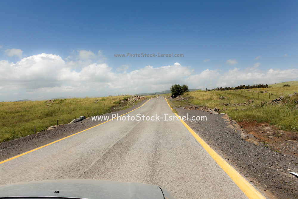 Straight road to vanishing point on the horizon with no traffic. Photographed in the Golan Heights, Israel