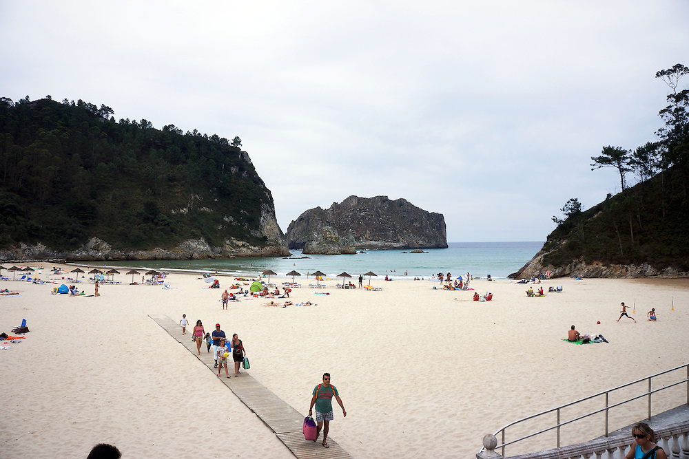 People leaving a beach on a cloudy day in Astaurias, Spain.