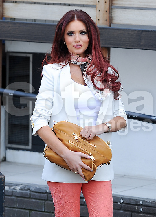 Red hair Amy Childs wearing a white blazer jacket and top with peach three quarter length trousers with matching orange shoes at ITV studios in London. UK. 23/04/2013<br />