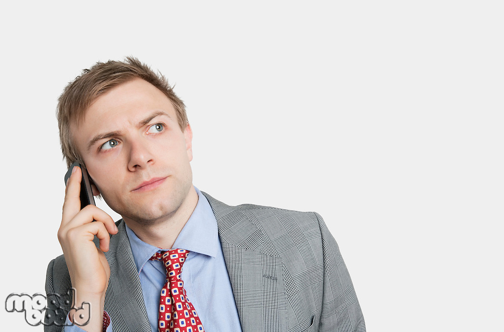 Handsome young businessman looking away while listening carefully to cell phone over colored background