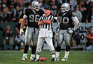 Darryl Russel, #90, talks behind the back of umpire Jim Quirk Sunday in the second half of the Raiders game against the Seahawks at Network Associates Coliseum with teammate Grady Jackson #90 during the second quarter. .