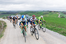 Lizzie Williams and Carmen Small grinning or grimmacing from ear to ear up the gravelled climb - Strade Bianche Elite Women 2016