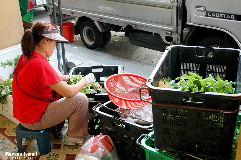 Vegetable vendor hard at work sorting out vegetables for the day