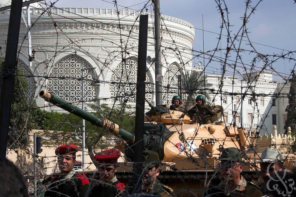 Egyptian military soldiers stand guard behind a barbed wire barricade outside the Orouba Presidential Palace February 11, 2011 in the Heliopolis district of Cairo, Egypt. Protesters marched Friday on a number of public buildings including the palace in an effort to spread their ongoing protests that are now in their 18th day. .(Photo by Scott Nelson)