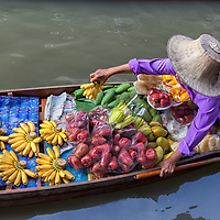 A woman selling fruits and vegetables on her boat at the floating market at Damnoen Saduak.
