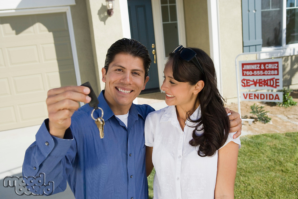 Young couple holding keys outside new home, portrait