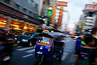 Tuk tuk taxis make their way along the frenetic and lively Yaowarat Road in Chinatown in Bangkok, Thailand.
