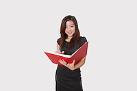 Portrait of beautiful young businesswoman writing notes in folder over white background