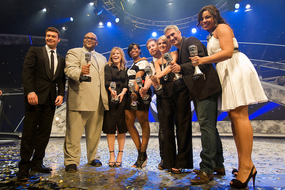 LAKE BUENA VISTA, FL - FEBRUARY 12:  Host Ryan Seacrest and all seven past American Idol winners Ruben Studdard, Kelly Clarkson, Fantasia Barrino, David Cook, Carrie Underwood, Taylor Hicks, and Jordin Sparks hold microphone awards given to them by creator Simon Fuller after the grand opening show of the American Idol Experience at Disney's Hollywood Studios In Walt Disney World on February 12, 2009 in Lake Buena Vista, Florida. (Photo by Matt Stroshane/Getty Images)