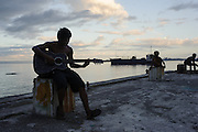 April 19, 2014 - Tacloban, Philippines. A young man plays guitar on a pier in Barangay 68, one of the neighbourhoods hardest hit by typhoon Haiyan. Typhoon Haiyan struck the central Philippines on November 8, 2013, leaving more than 5000 dead and displacing nearly 2 million people homeless.