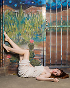 Fashion model Federica Ferrari reclines on sidewalk in front of desert-themed graffiti art wall.