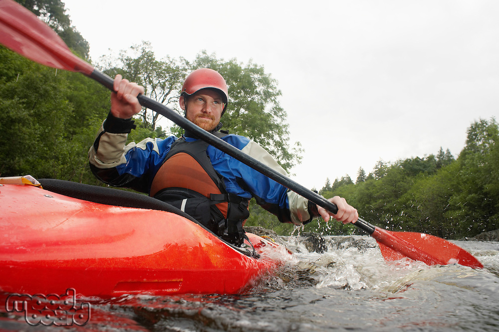 Man kayaking in river
