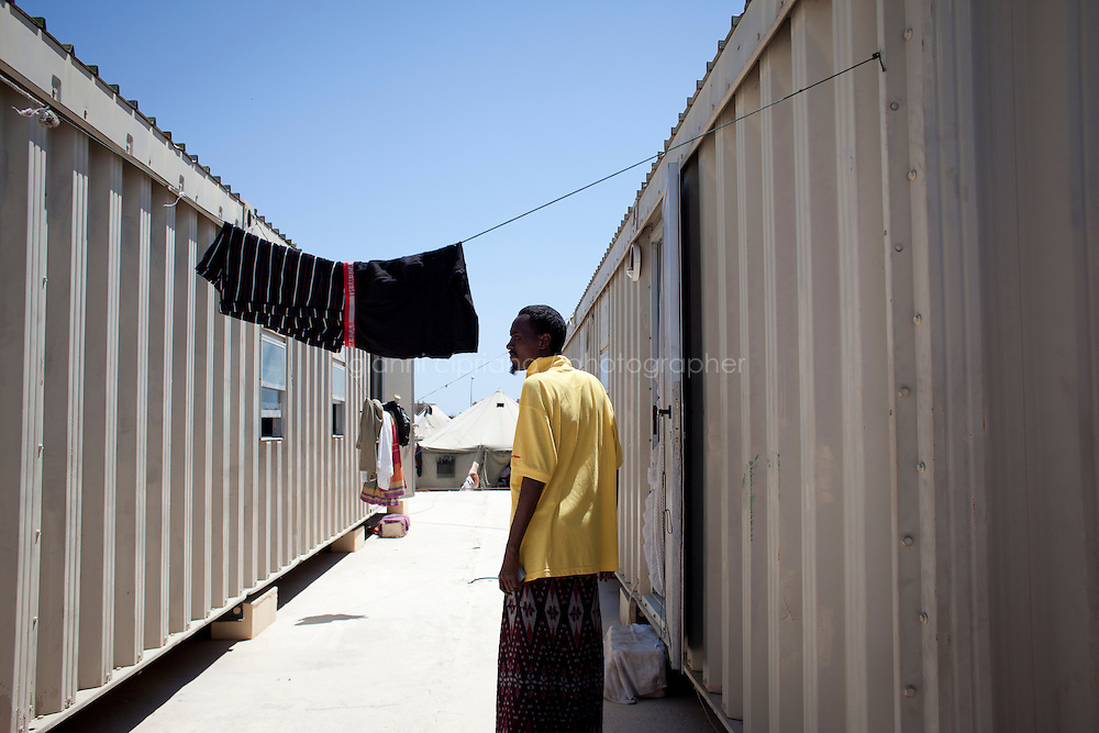 HAL FAR, MALTA - JUNE 21: A Sudanese immigrant between two containers of immigrants at the Tent Village, an open centre in Hal Far (which translates as &quot;Rat's Town&quot;) on June 21, 2011. The Open Centres in Malta serve as a temporary accomodation facility, but they ended becoming permanent accomodation centres, except for those immigrants who receive subsidiary protection or refugee status and that are sent to countries such as the United States, Germany, Poland, and others. All immigrants who enter in Malta illegally are detained. Upon arrival to Malta, irregular migrants and asylum seekers are sent to one of three dedicated immigration detention facilities. Once apprehended by the authorities, immigrants remain in detention even after they apply for refugee status. detention lasts as long as it takes for asylum claims to be determined. This usually takes months; asylum seekers often wait five to 10 months for their first interview with the Refugee Commissioner. Asylum seekers may be detained for up to 12 months: at this point, if their claim is still pending, they are released and transferred to an Open Center.<br /> <br /> Gianni Cipriano for The New York Times