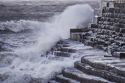 © Licensed to London News Pictures. Aberystwyth, UK. 27/01/2019. Gale force, and bitterly cold, north-westerly winds blowing at up to 70mph  drive huge waves into the sea defences at Aberystwyth in west Wales. A yellow Met Office warning for high winds has been issued covering all of Wales and much of the wet of the UK today. Photo credit Keith Morris/LNP