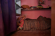 The house which Simram (L), owns contains one room and a tiny kitchen. (Sebnam (R), In this room they live and sleep. Varanasi, India.