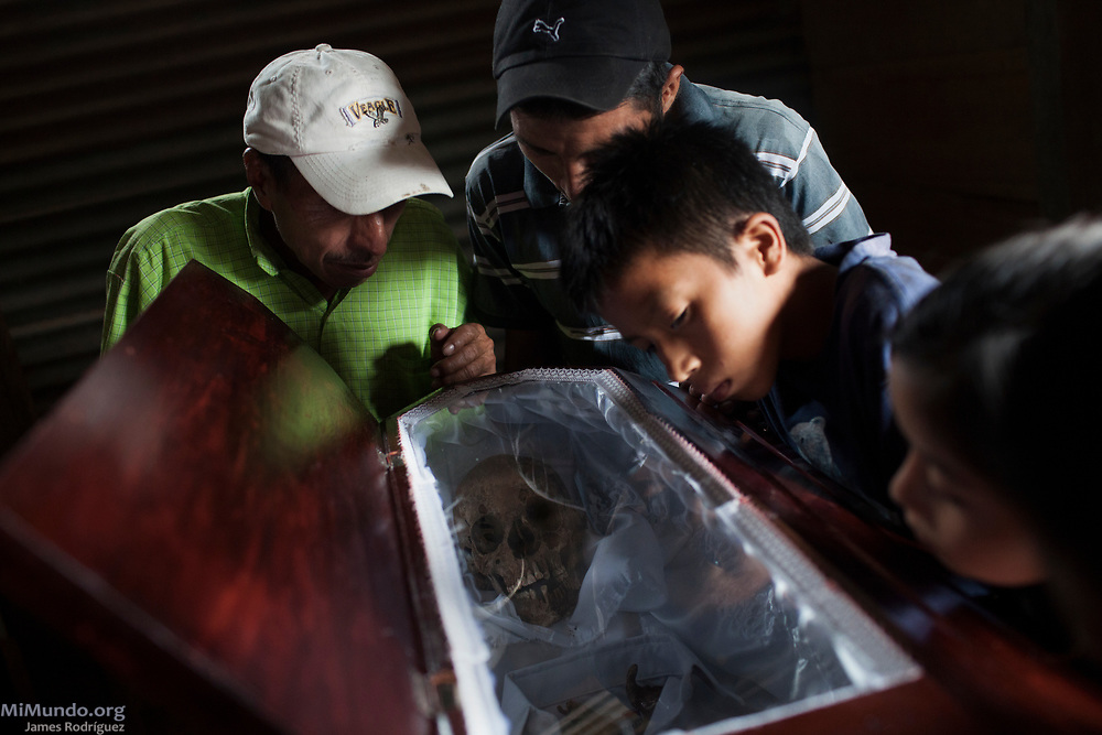 Locals from Pinares hamlet look into a coffin containing the remains of Agustin Tec Pop, exhumed from Coban's former Military Zone 21 in August 2012. On September 13, 1983, Tec Pop and three others were fleeing violence when they were taken captive by an army platoon they encountered in the mountains near Chi'is. Tec Pop's remains were identified through DNA analysis by members of the Forensic Anthropology Foundation of Guatemala (FAFG) and returned to his family members in October 2014. Pinares, Cahabon, Alta Verapaz, Guatemala. October 30, 2014.