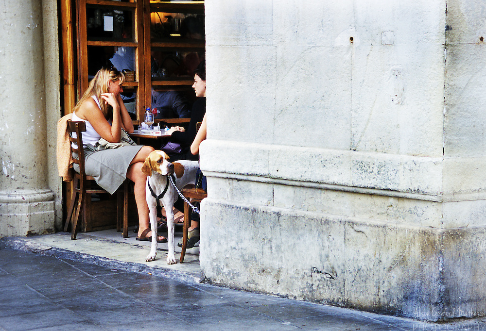 Two women and their dog chat over a coffee in a Barcelona cafe.