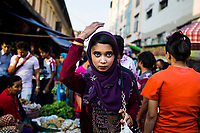 A young Burmese woman walks through a street market in downtown Yangon, Myanmar.