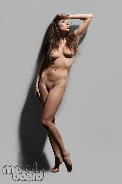 Naked young woman standing on toes over gray background.