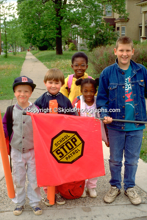 Kids waiting to cross street behind school patrol flag age 6 through 12.  St Paul  Minnesota USA