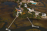 Aerial view of waterfront homes and long docks along the marsh in Charleston, SC.