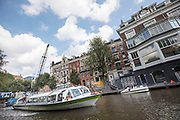 In Amsterdam vaart een hop-on hop-off rondvaartboot door de Singelgracht.<br /> <br /> In Amsterdam a hop-on hop-off boat sails at the Singelgracht.