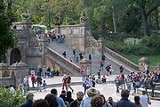 Large groups of people walk around the Bethesda Terrace and Fountain in Central Park, New York City.