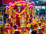 "02 JUNE 2017 - SAMUT SAKHON, THAILAND: Men carry the City Pillar Shrine to waiting boats in Samut Sakhon. The Chaopho Lak Mueang Procession (City Pillar Shrine Procession) is a religious festival that takes place in June in front of city hall in Samut Sakhon. The ""Chaopho Lak Mueang"" is  placed on a fishing boat and taken across the Tha Chin River from Talat Maha Chai to Tha Chalom in the area of Wat Suwannaram and then paraded through the community before returning to the temple in Samut Sakhon. Samut Sakhon is always known by its historic name of Mahachai.      PHOTO BY JACK KURTZ"