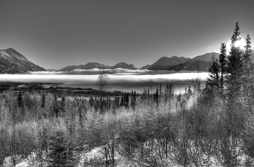 A layer of fog lays over Skilak Lake below the Kenai Mts. best displayed in black and white contrast.