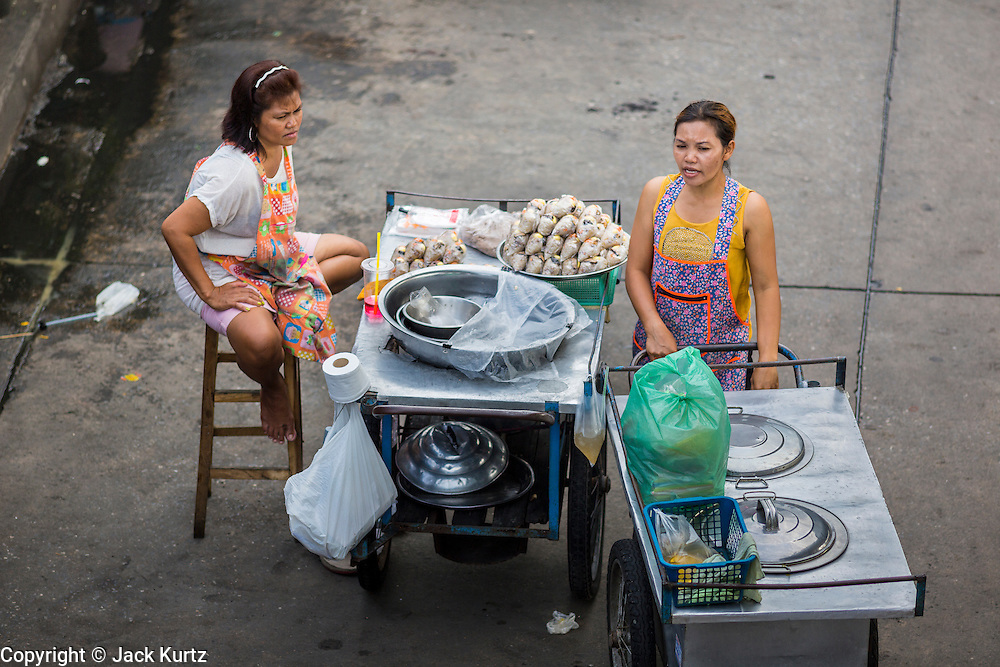 """24 AUGUST 2013 - BANGKOK, THAILAND: Food cart operators wait for customers on a street in Bangkok. Thailand entered a """"technical"""" recession this month after the economy shrank by 0.3% in the second quarter of the year. The 0.3% contraction in gross domestic product between April and June followed a previous fall of 1.7% during the first quarter of 2013. The contraction is being blamed on a drop in demand for exports, a drop in domestic demand and a loss of consumer confidence. At the same time, the value of the Thai Baht against the US Dollar has dropped significantly, from a high of about 28Baht to $1 in April to 32THB to 1USD in August.    PHOTO BY JACK KURTZ"""
