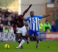 Photo: Jed Wee.<br />Wigan Athletic v Arsenal. The Barclays Premiership.<br />19/11/2005.<br />Arsenal's Lauren (L) and Wigan's Jason Roberts challenge for possession.