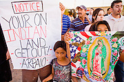 03 APRIL 2008 -- GUADALUPE, AZ:  CRUZ SANCHEZ, left, and his nieces, JULIA MARTINEZ, 4, and FLORENTINA MARTINEZ, 8, all Native Americans from Guadalupe, AZ, protest against Maricopa County Sheriff Joe Arpaio Thursday. The Maricopa County Sheriff's Department has started high profile zero tolerance crime sweeps targeting illegal immigrants but also arresting anyone they find breaking the law or with outstanding warrants. All of the previous sweeps have been in Phoenix city limits. This was the first one outside Phoenix, Guadalupe is a working class unincorporated town south of Phoenix. Most of the town's residents are Native Americans and Hispanics and hundreds of people lined the street to protest the sweep.  In 2011, the US Department of Justice issued a report highly critical of the Maricopa County Sheriff's Department and the jails. The DOJ said the Sheriff's Dept. engages in widespread discrimination against Latinos during traffic stops and immigration enforcement, violates the rights of Spanish speaking prisoners in the jails and retaliates against the Sheriff's political opponents.     PHOTO BY JACK KURTZ