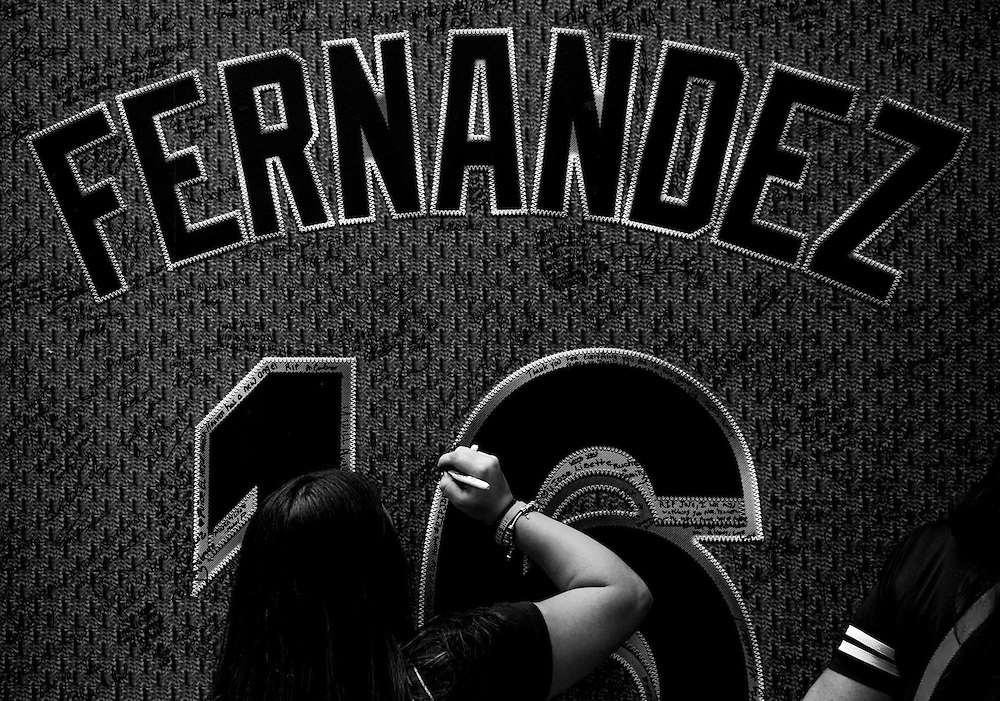 As many wait in line, a fan signs a tribute wall honoring Jose Fernandez outside Marlins Park.