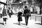 A husband and a wife take an afternoon stroll on Me'a She'arim Street in Jerusalem. From the clothing you can assess the couple belong to the Satmar current of orthodox Jews.
